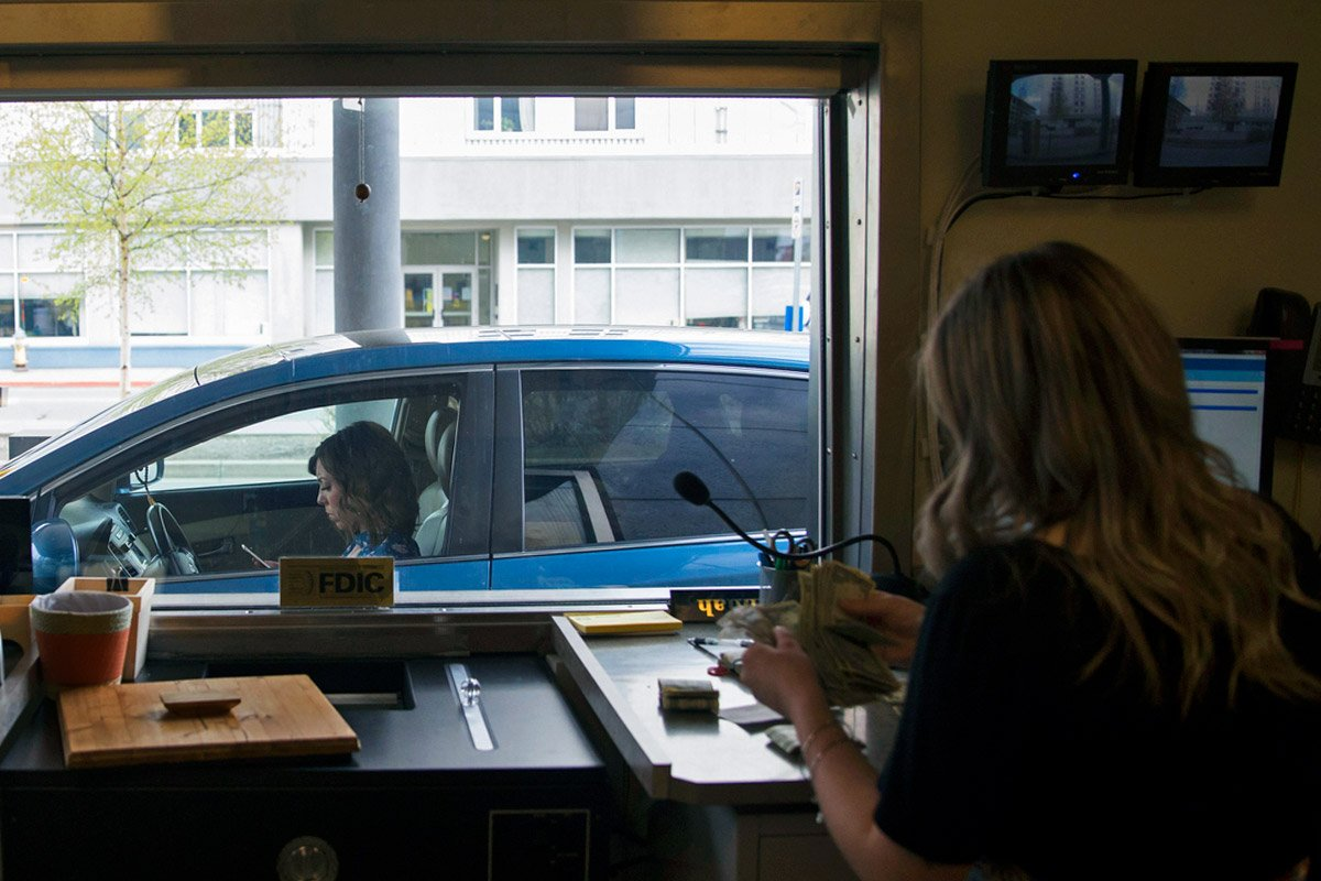 A woman in a car is server at a bank drive-thru window.